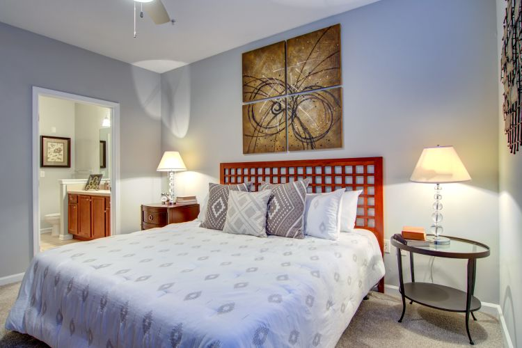 Master bedroom with an accent wall and an en suite bathroom in a model home at Landing Square in Atlanta, Georgia