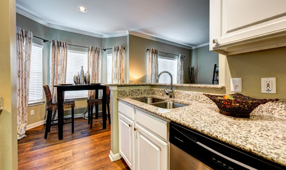 Kitchen with granite countertops and white cabinetry in a model home at Baypoint in Corpus Christi, Texas