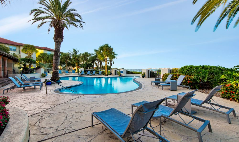 Swimming pool area with chaise lounge chairs at Baypoint in Corpus Christi, Texas