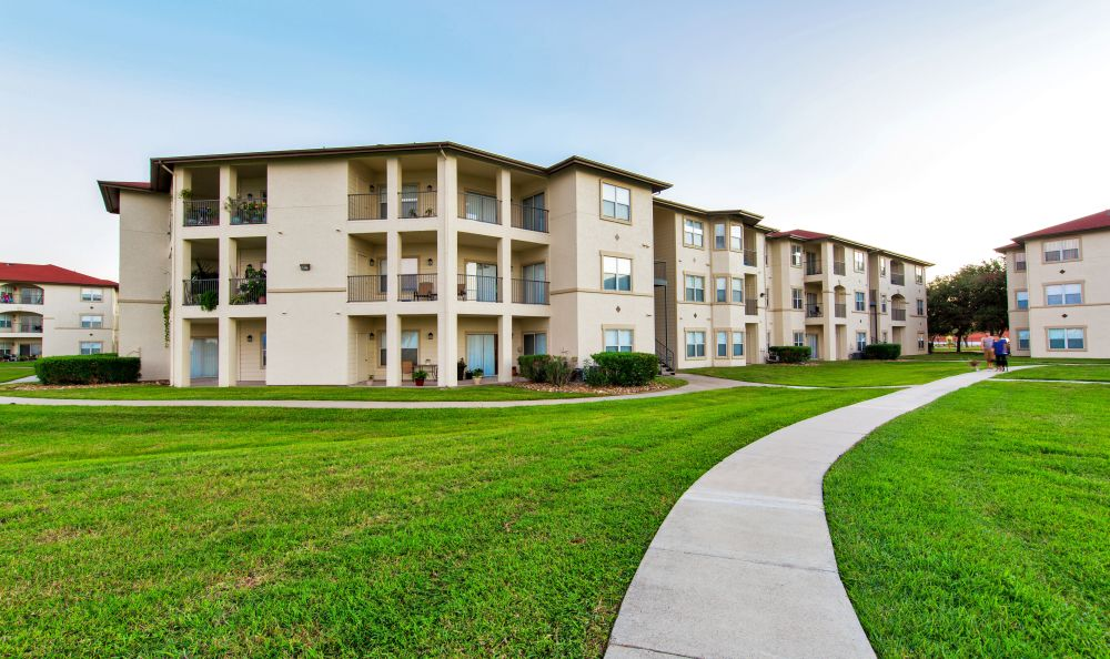 Green grass and walking paths among resident buildings at Baypoint in Corpus Christi, Texas