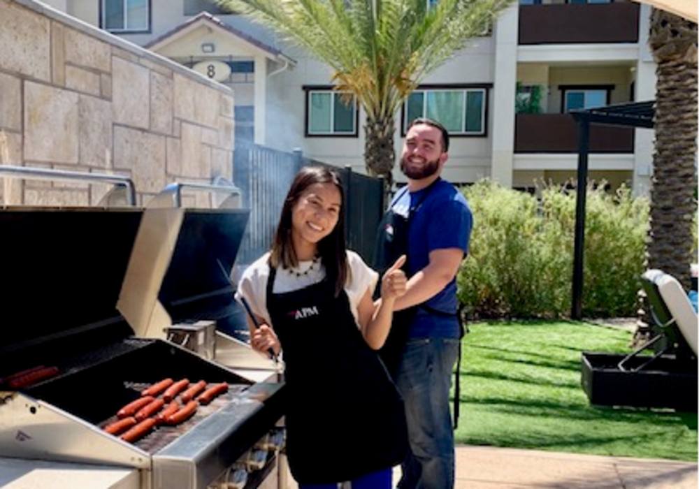 Two of the community team members grilling up hot dogs on a beautiful day at a property managed by American Property Management in Bellevue, Washington