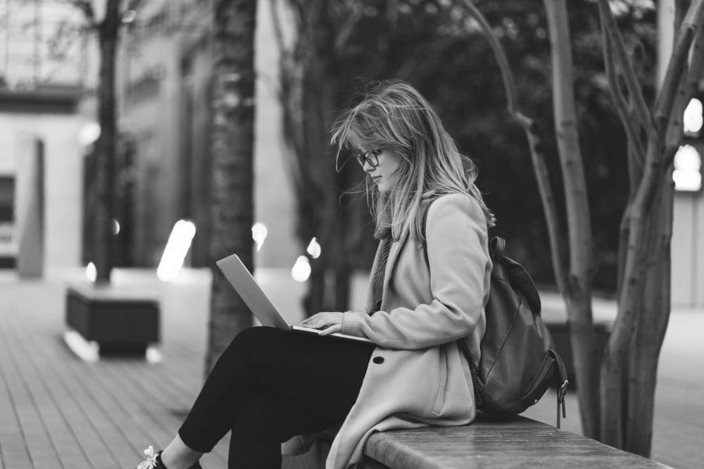 Resident working on her laptop outside near IDENTITY Boise in Boise, Idaho