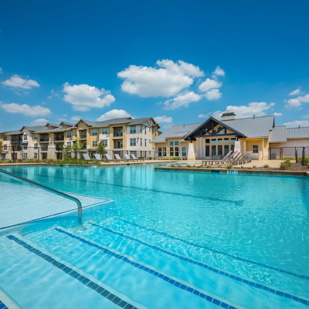 Gorgeous swimming pool area on a beautiful day at 4 Corners Apartments in Frisco, Texas