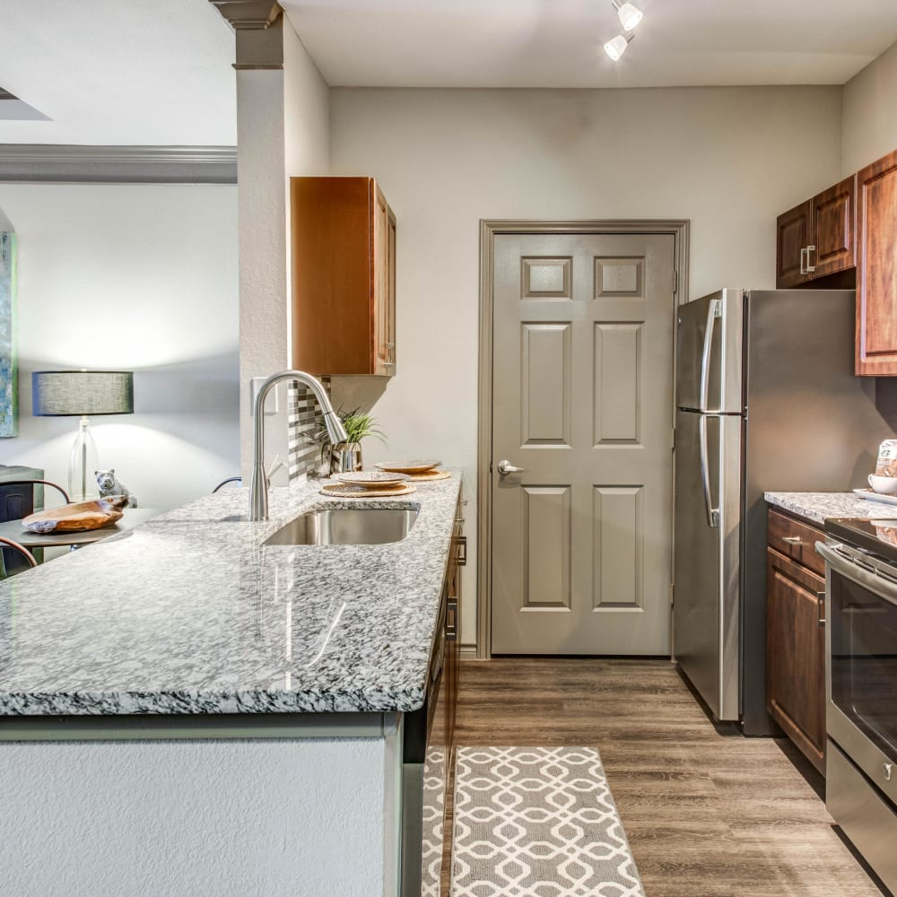Granite countertops and dark wood cabinetry in model home's kitchen at Beck at Wells Branch in Austin, Texas