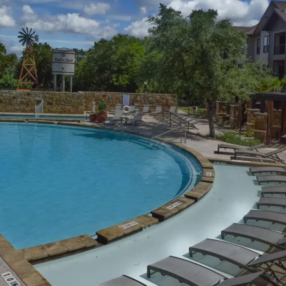 Poolside lounge chairs surrounded by greenery at The Asten at Ribelin Ranch in Austin, Texas