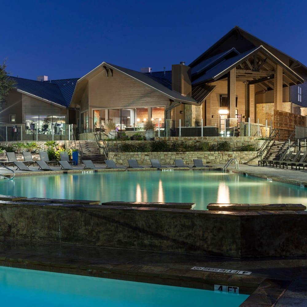 Dimly lit swimming pool at dusk at The Asten at Ribelin Ranch in Austin, Texas