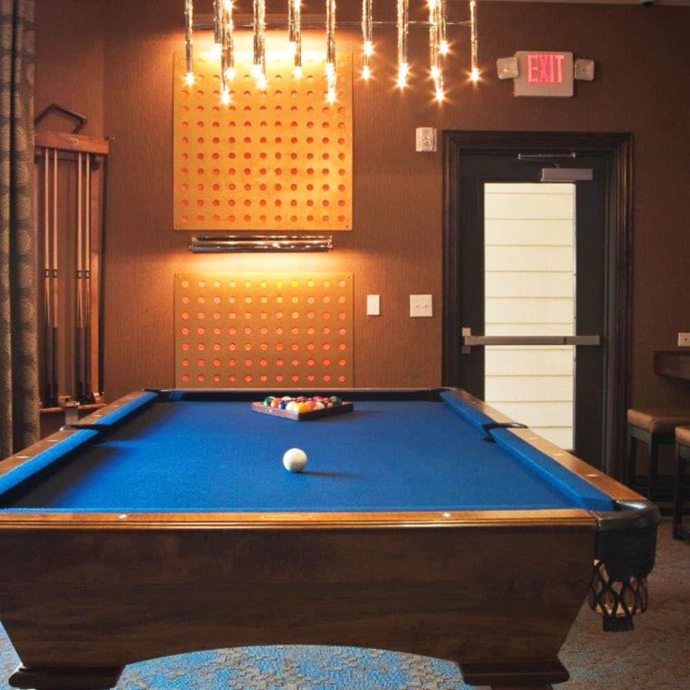 Community clubhouse with a billiard table and bar seating at The Blvd in Irving, Texas