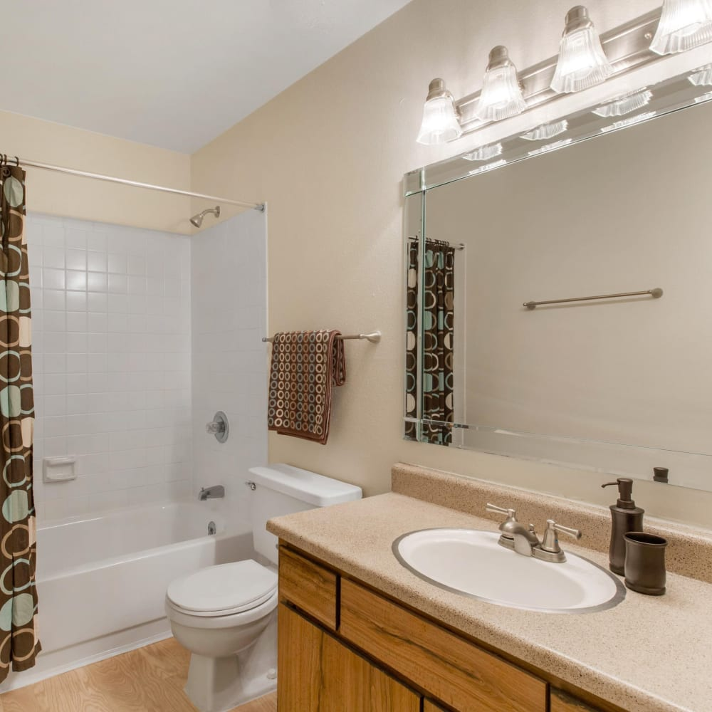 Bathroom with a large vanity mirror and an oval tub at Finley West in Houston, Texas