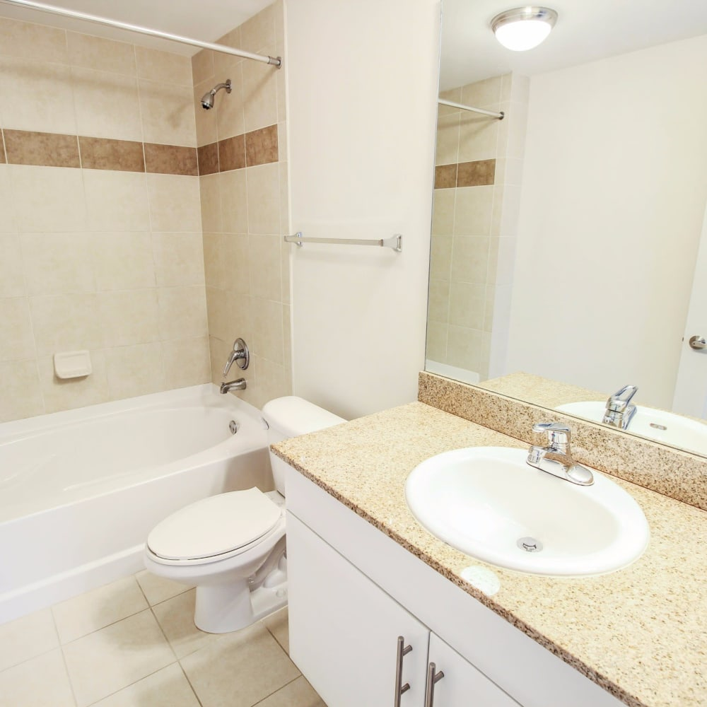Spacious bathroom with a large vanity mirror at Midtown 24 in Plantation, Florida