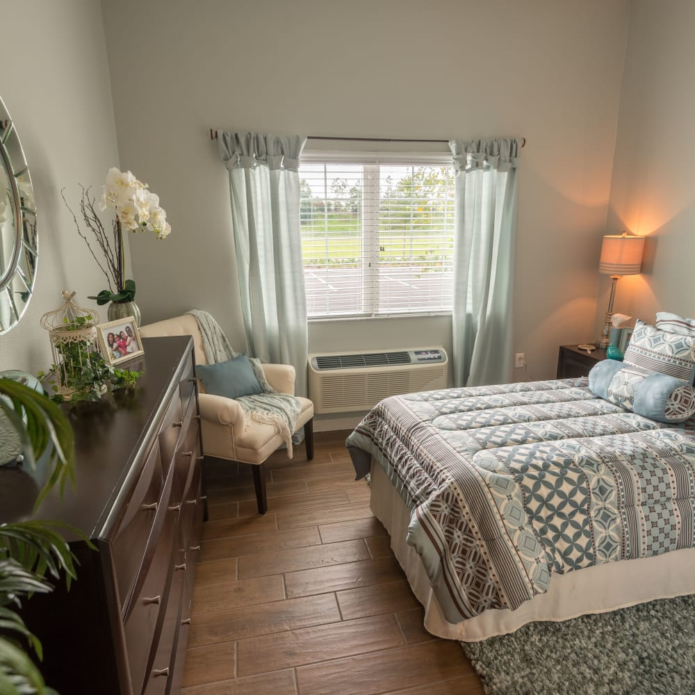 Resident bedroom with a large window at Inspired Living Lewisville in Lewisville, Texas