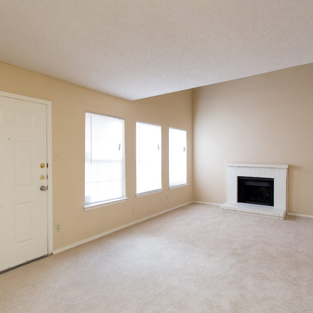 Living room with a fireplace and three large windows at Canopy on Central in Bedford, Texas