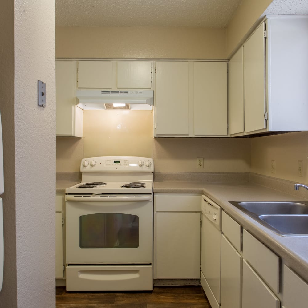 Kitchen with white cabinetry and appliances at Canopy on Central in Bedford, Texas