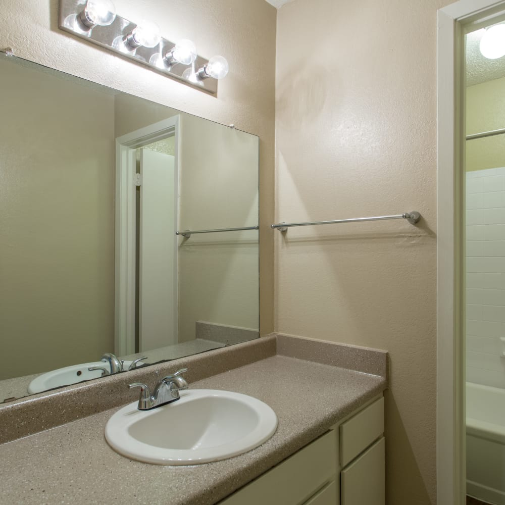 Bathroom with a large vanity mirror at Canopy on Central in Bedford, Texas