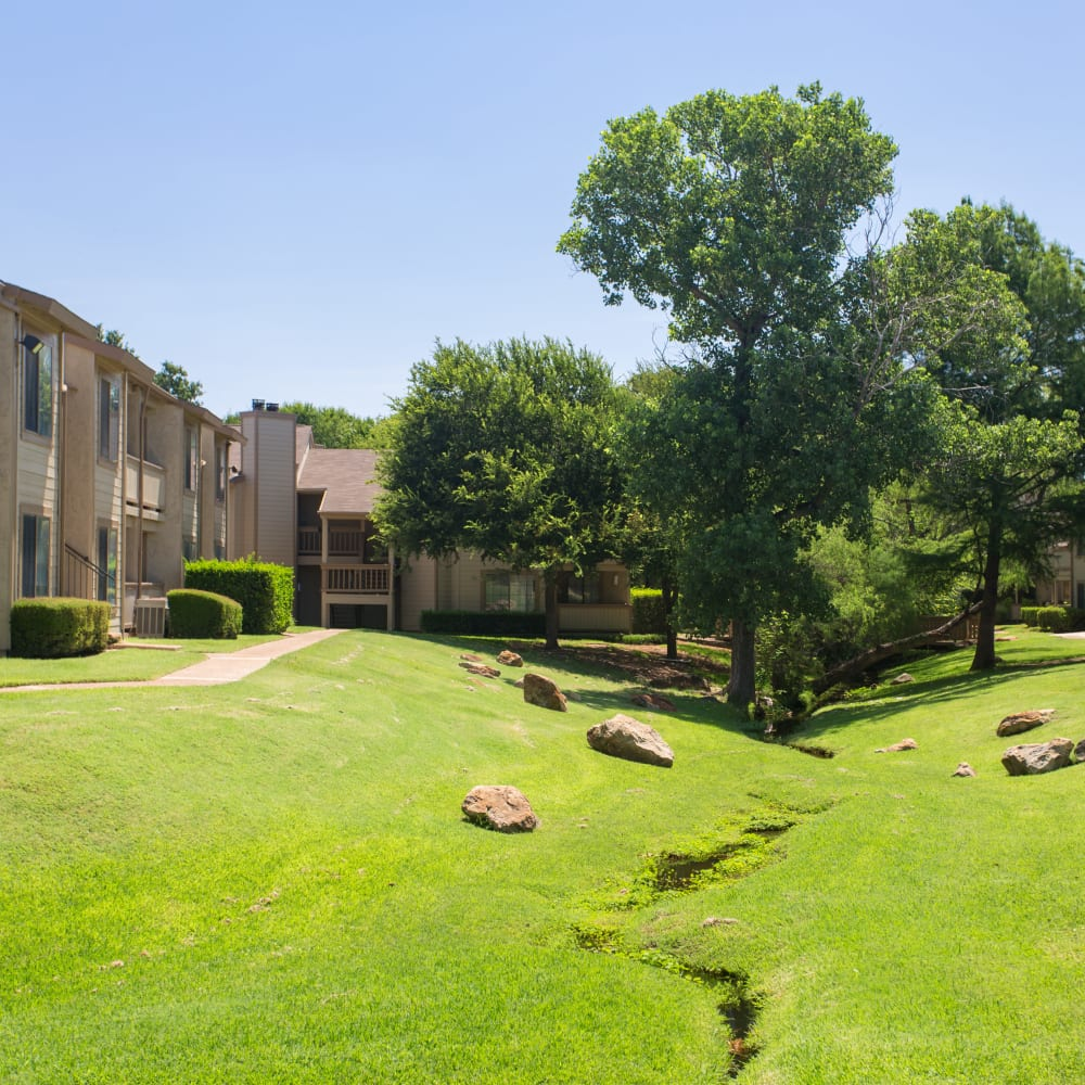 Open grass lawn with a creek at Canopy on Central in Bedford, Texas