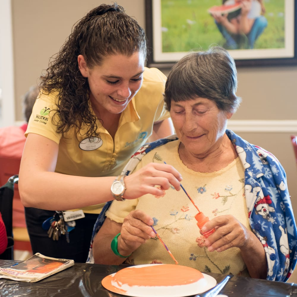 Staff member helping a resident with an art project at Inspired Living.