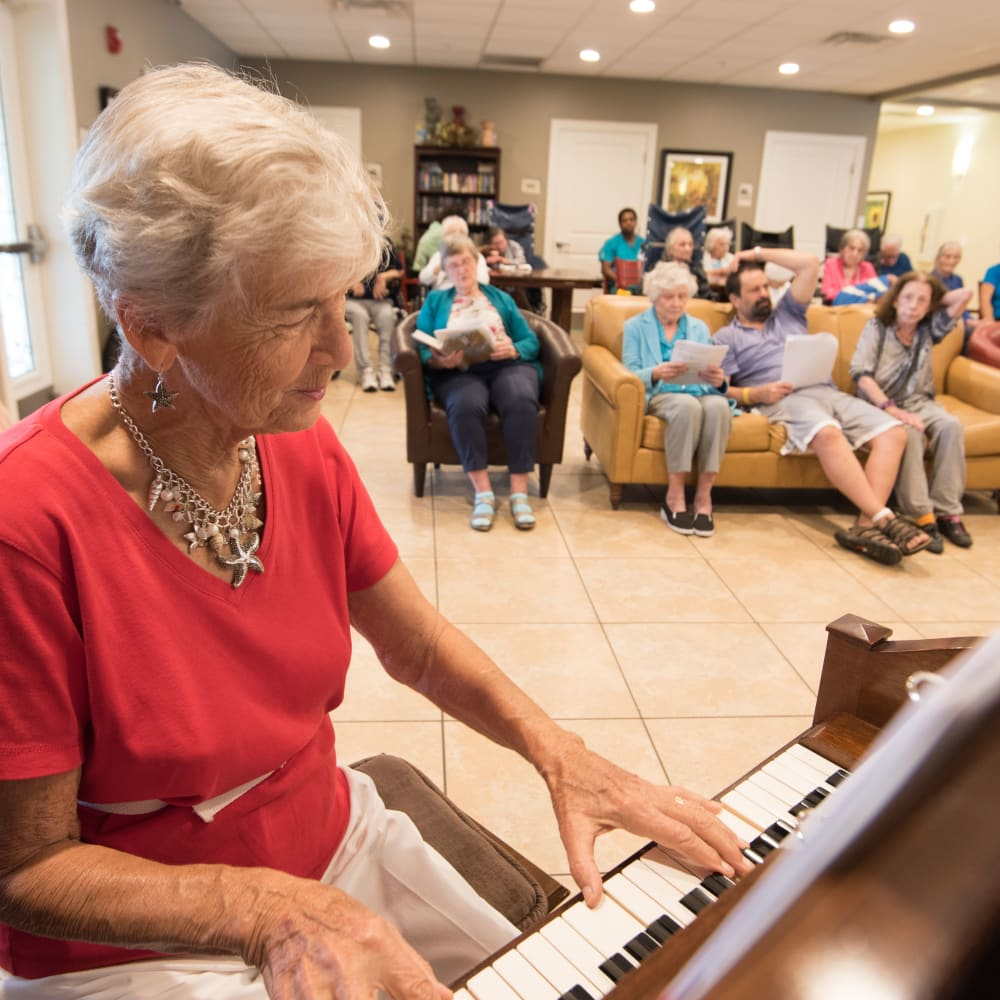 A Inspired Living resident playing the piano for other residents.