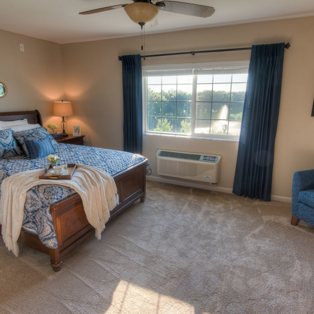 Resident bedroom with natural light at Inspired Living Lakewood Ranch in Bradenton, Florida.