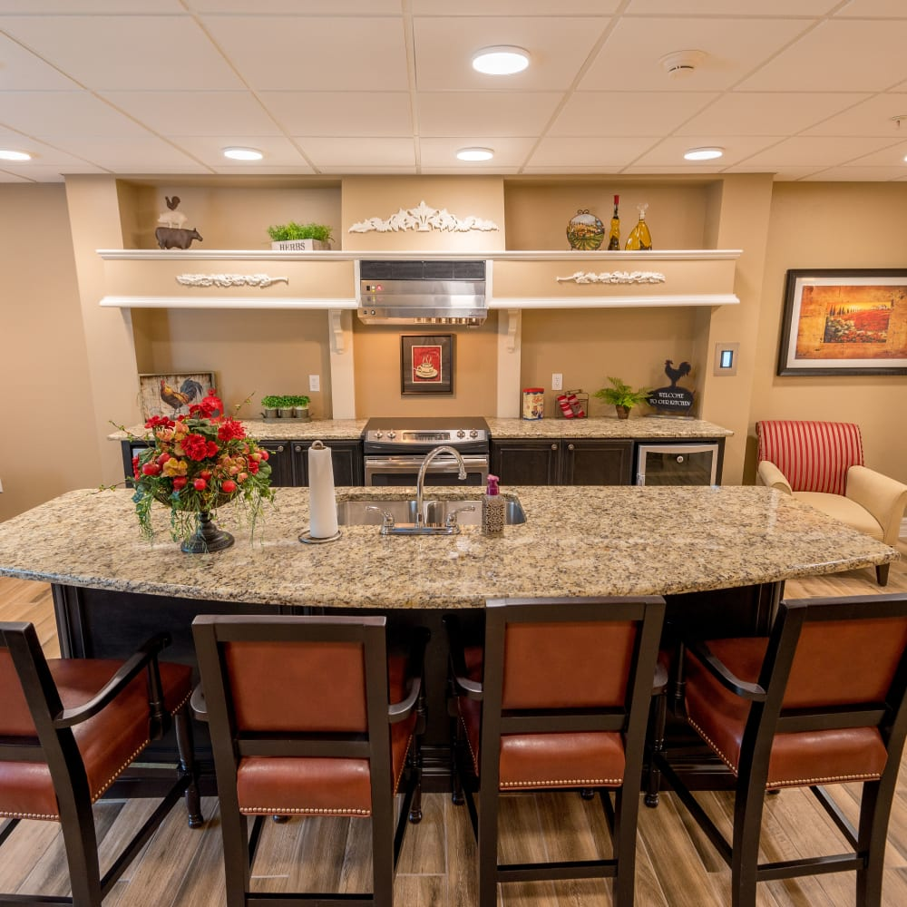 Family dining room with a long table and kitchenette at Inspired Living at Royal Palm Beach in Royal Palm Beach, Florida