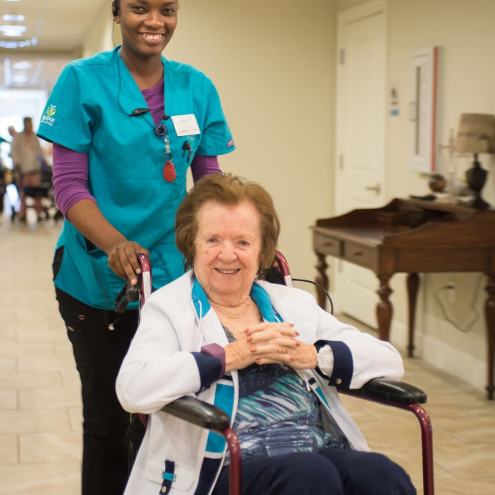 Staff member helping a resident in a wheelchair at Inspired Living Royal Palm Beach in Royal Palm Beach, Florida.
