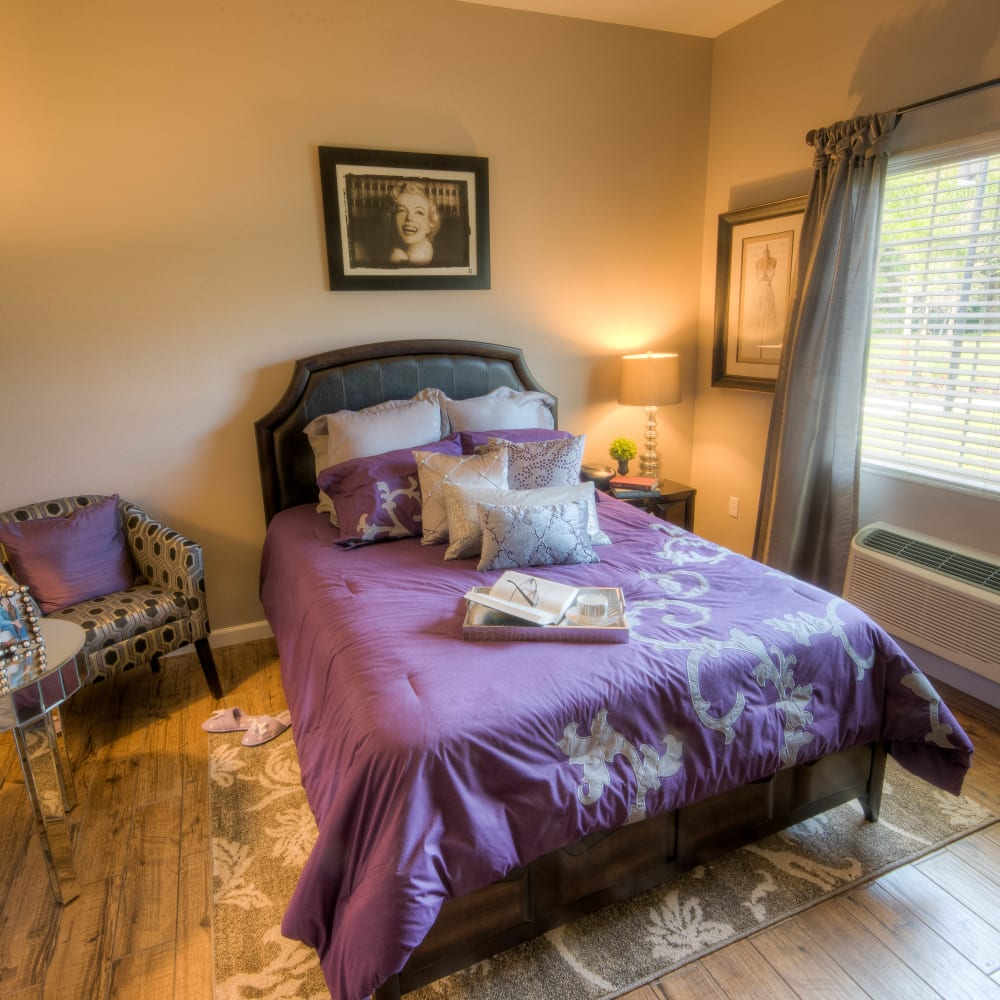 A resident bedroom with hardwood floors at Inspired Living Tampa in Tampa, Florida