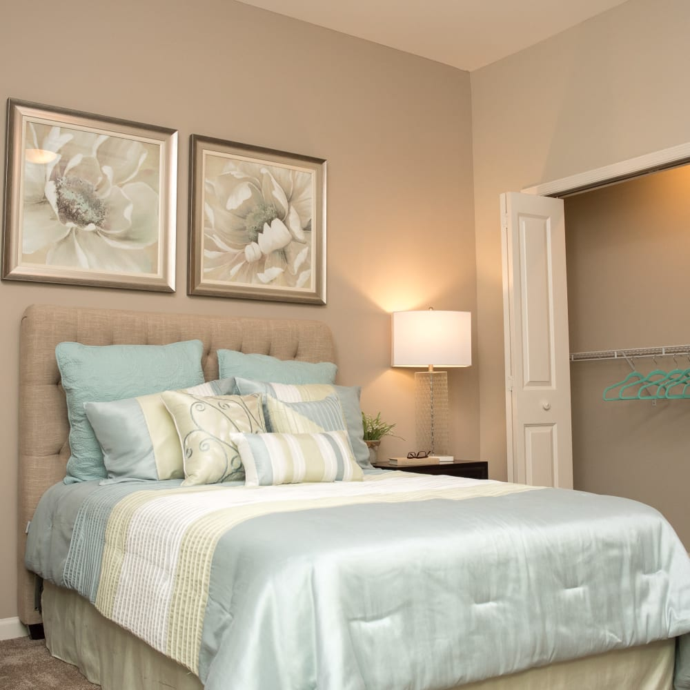Resident bedroom with a closet and wall art at Inspired Living Sugar Land in Sugar Land, Texas