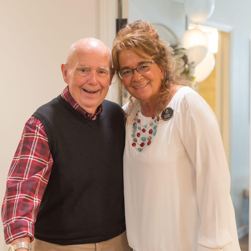 A resident poses for a picture with a staff member at Inspired Living Ivy Ridge in St Petersburg, Florida