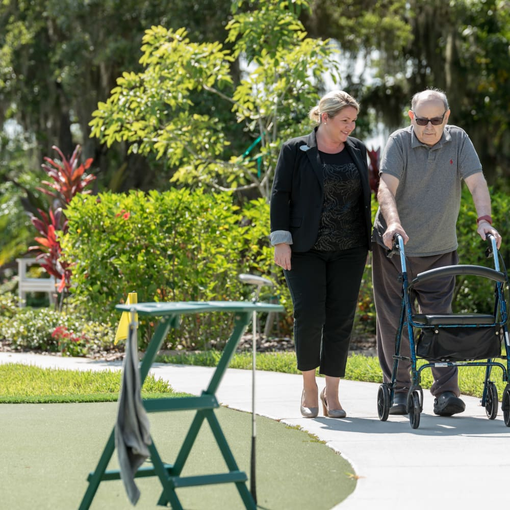 A resident and a staff member on a walk near Inspired Living Royal Palm Beach in Royal Palm Beach, Florida