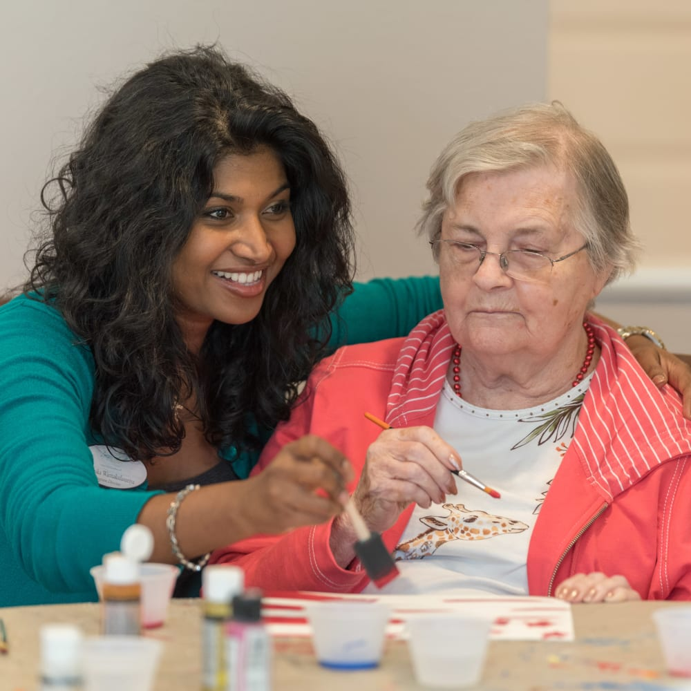 A staff member helping a resident paint at Inspired Living in Lewisville, Texas