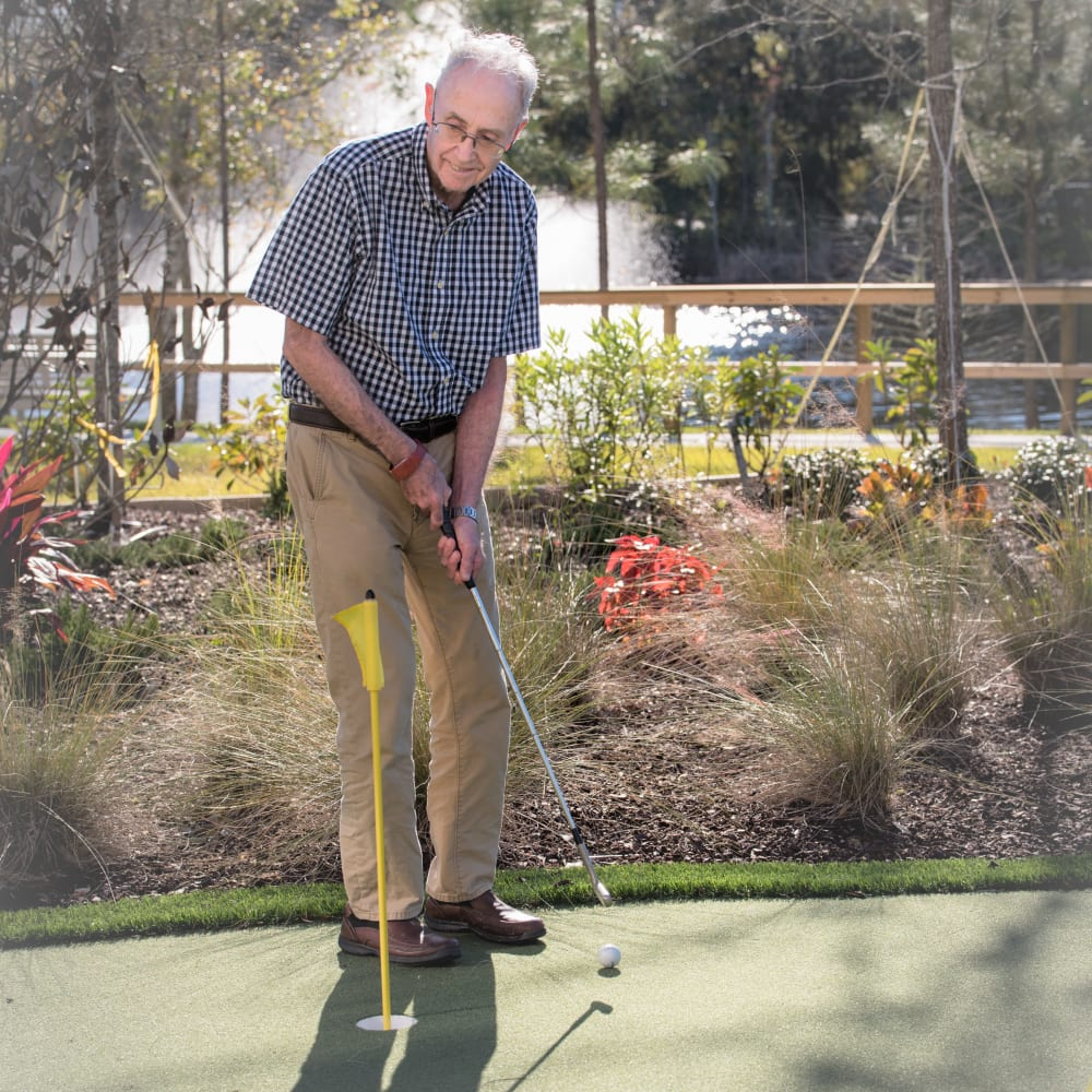 A resident on the putting green at Inspired Living Lewisville in Lewisville, Texas.