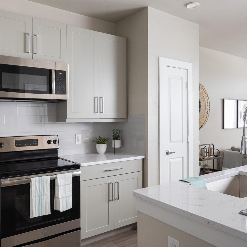 42-Inch gray shaker-style cabinetry with chrome accents in kitchen at Opal at Barker Cypress in Houston, Texas