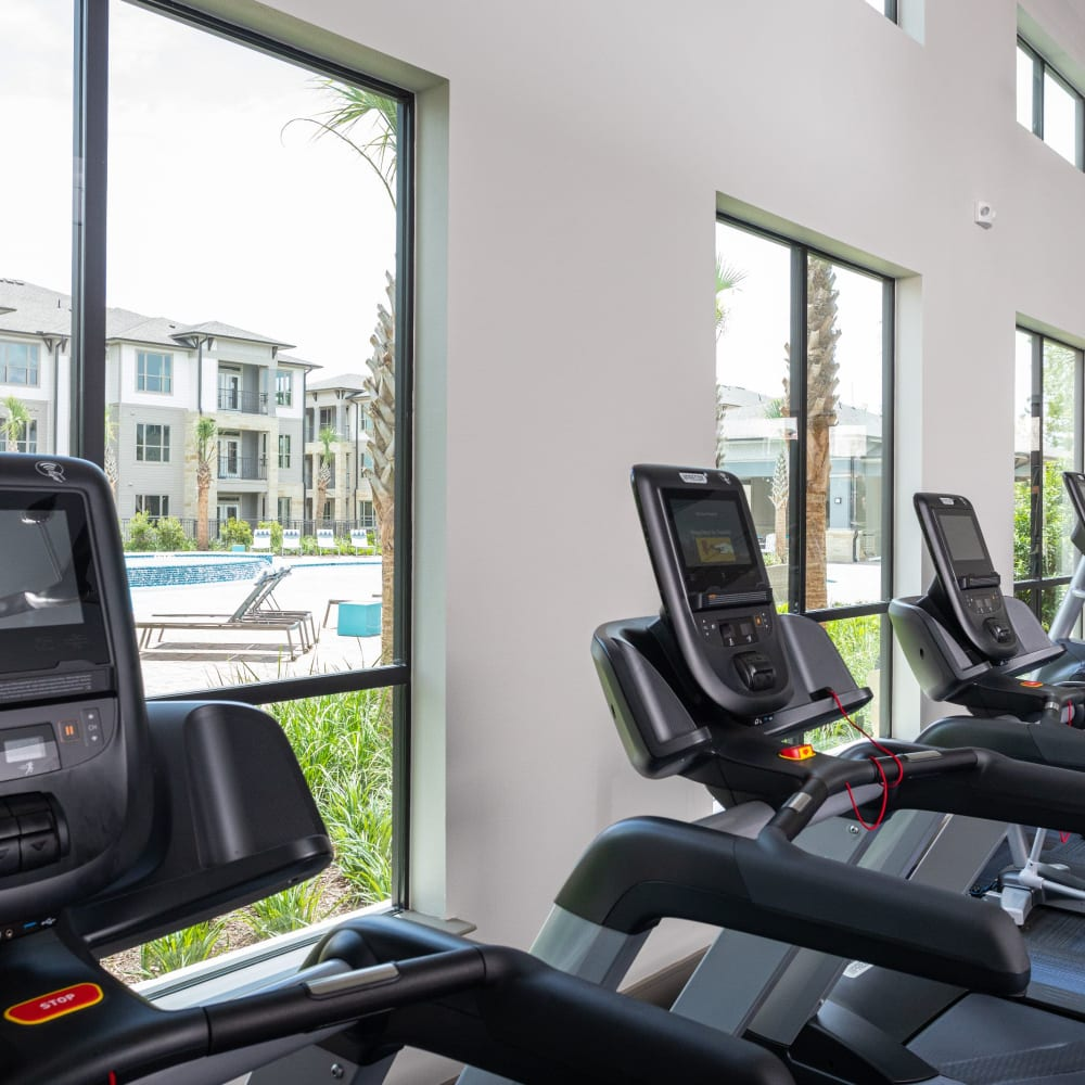 Fitness center with large windows at Opal at Barker Cypress in Houston, Texas