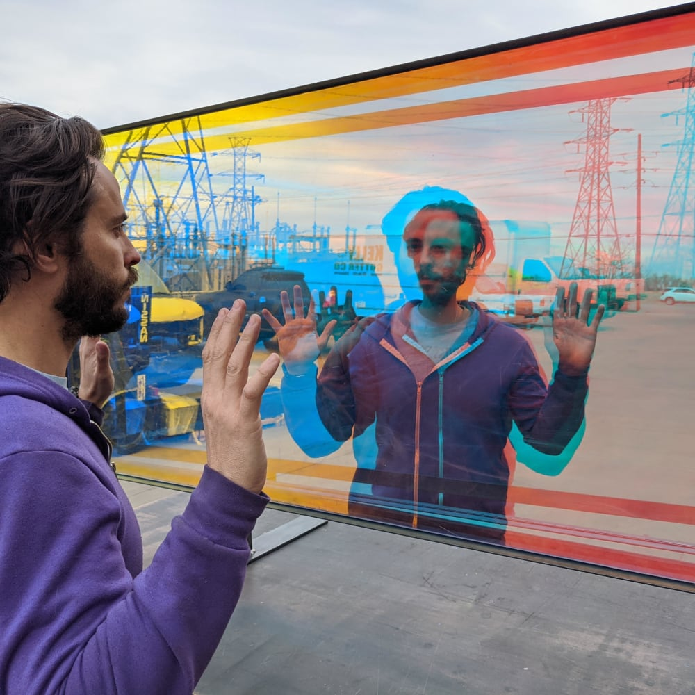 Man looking at reflection with hands in air