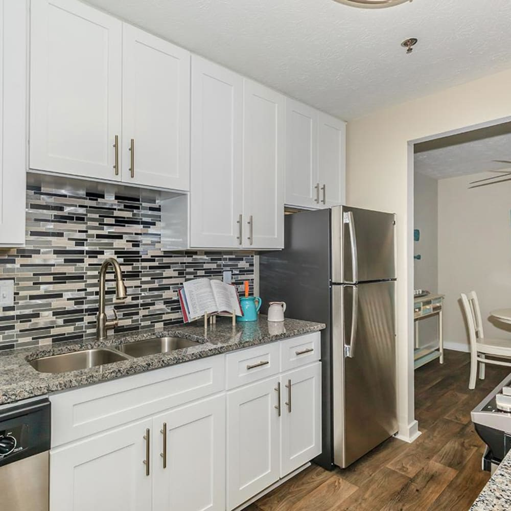Beautiful kitchen with hardwood flooring and a subway tile backsplash in a model apartment at The Bentley at Marietta in Marietta, Georgia