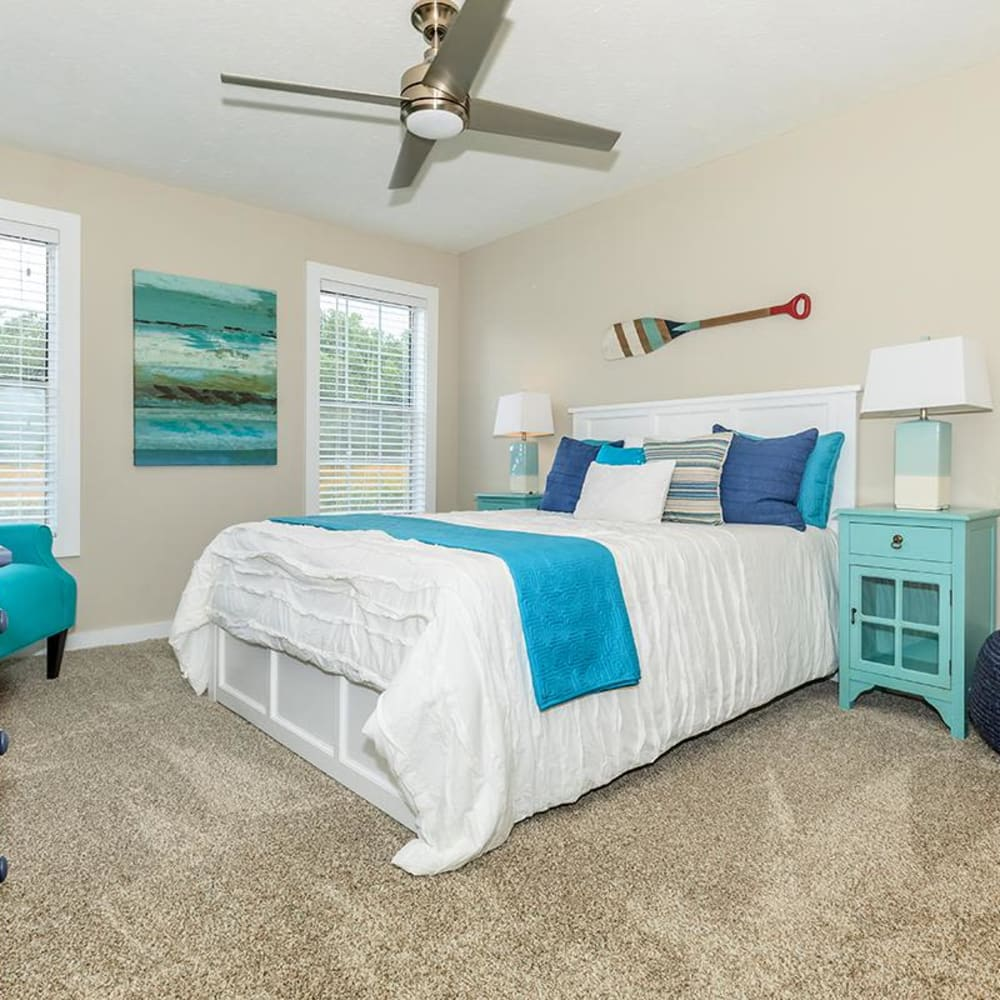 Large master bedroom with plush carpeting and bay windows in a model home at The Bentley at Marietta in Marietta, Georgia