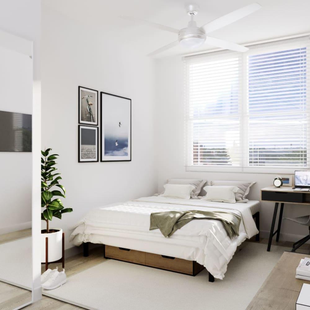Bright bedroom with wood-style flooring at UNCOMMON Auburn in Auburn, Alabama