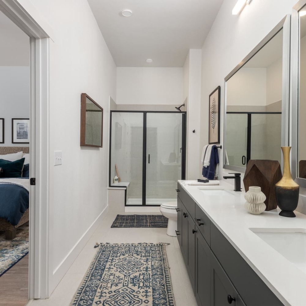 Dual sinks and a glass-enclosed shower in the primary bathroom of a model home at 4600 Ross in Dallas, Texas