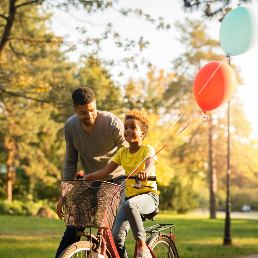 Father teaching his child how to ride a bike at Oaks Minnehaha Longfellow in Minneapolis, Minnesota