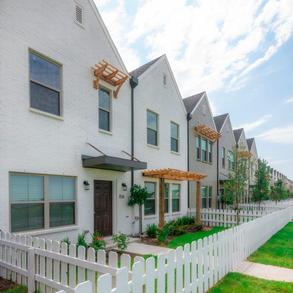 White picket fences and green grass of the town homes at The Townhomes at BlueBonnet Trails in Waxahachie, Texas