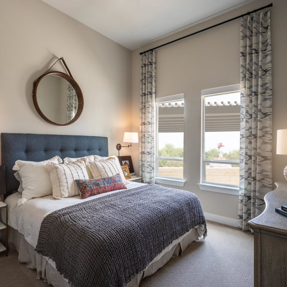 Well-furnished model apartment's bedroom with large bay windows at Magnolia Heights in San Antonio, Texas