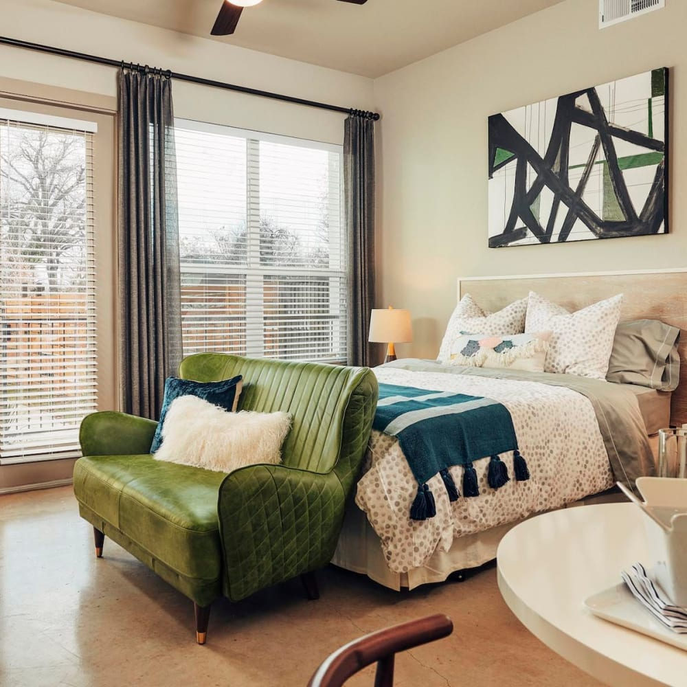 Concrete flooring and a ceiling fan in a model home's bedroom at The Guthrie in Austin, Texas