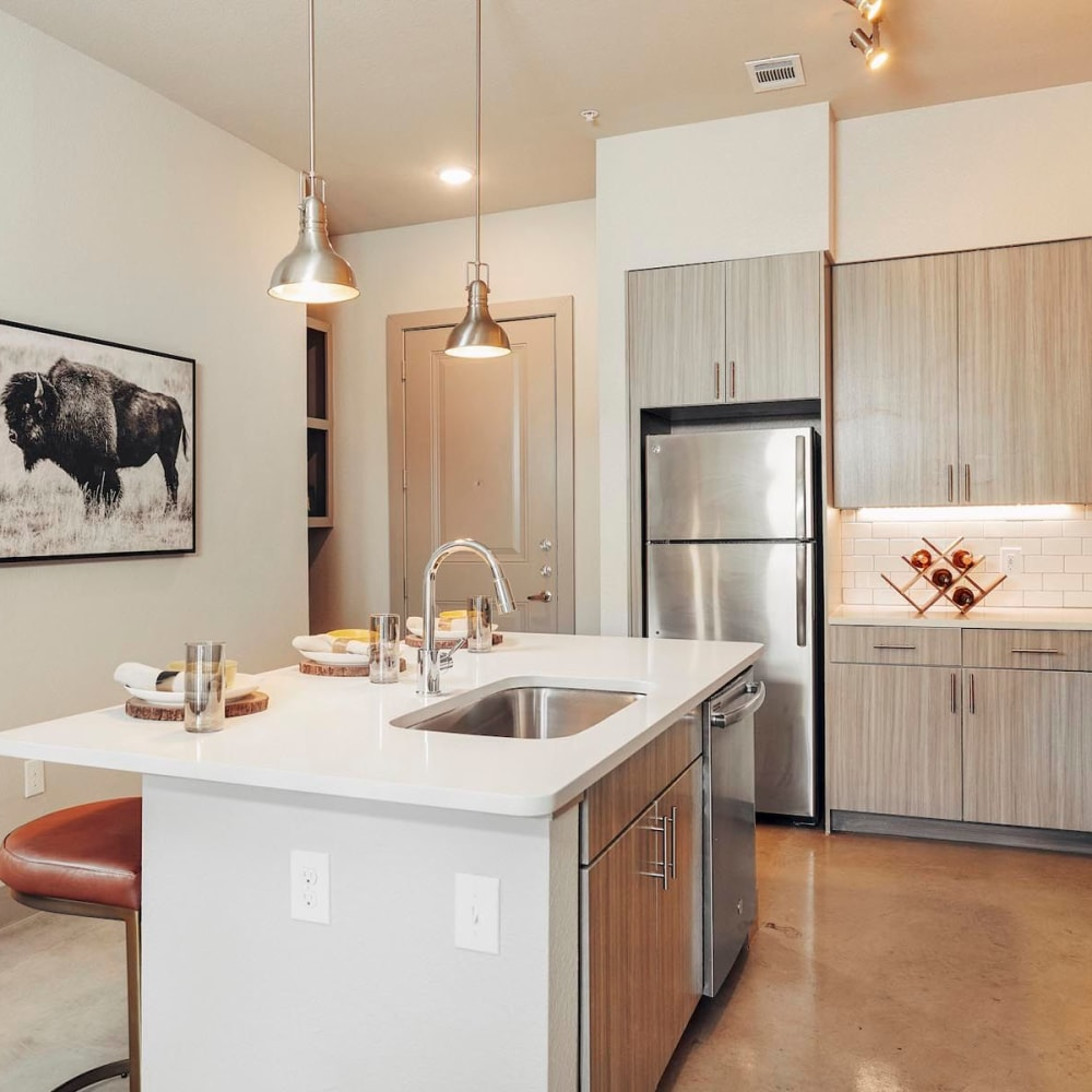 Model home's kitchen with quartz countertops and an island at The Guthrie in Austin, Texas