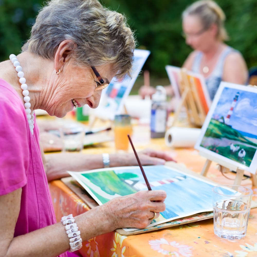 Residents having fun painting at Inspired Living Delray Beach in Delray Beach, Florida