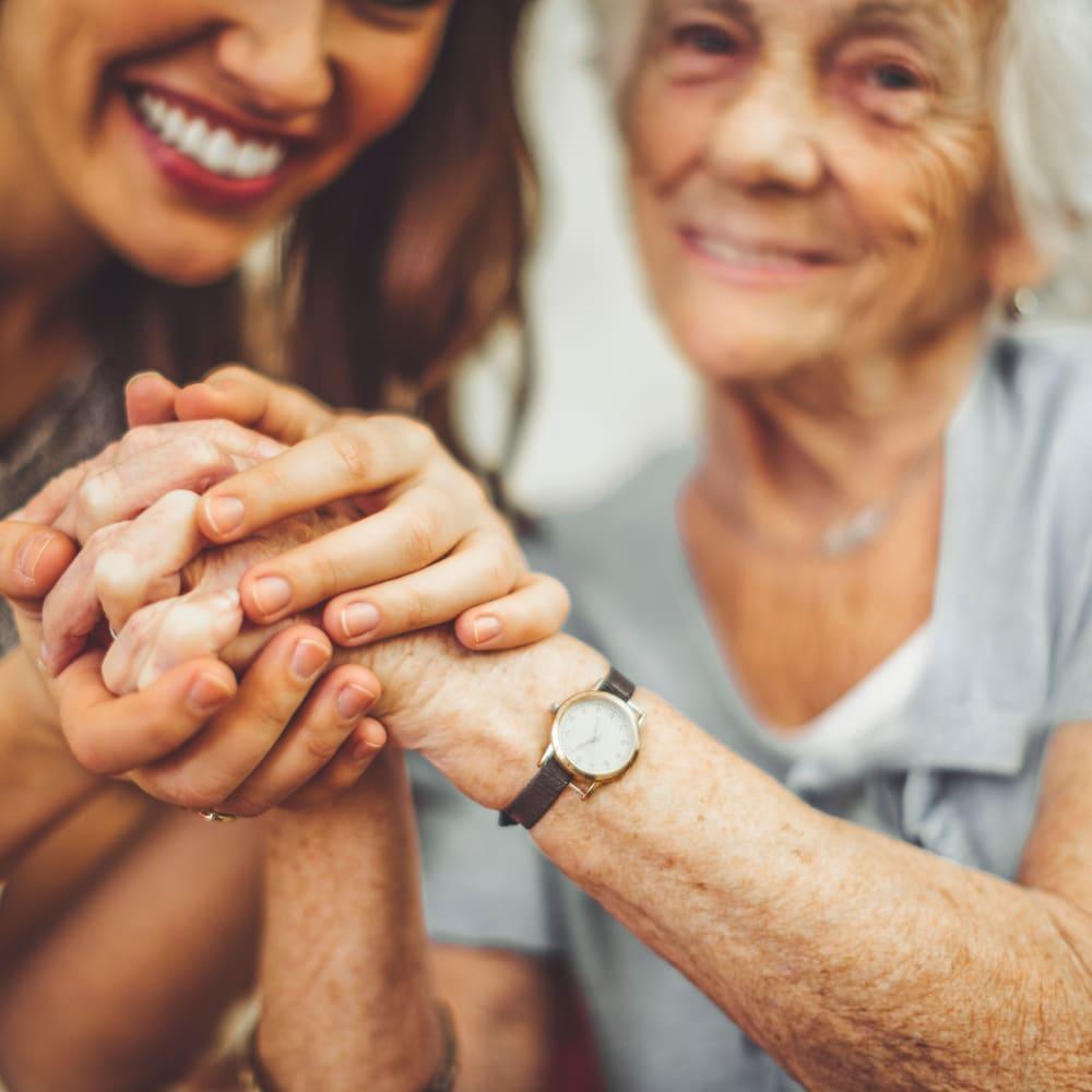 A caregiver and a resident holding hands at Inspired Living Delray Beach in Delray Beach, Florida