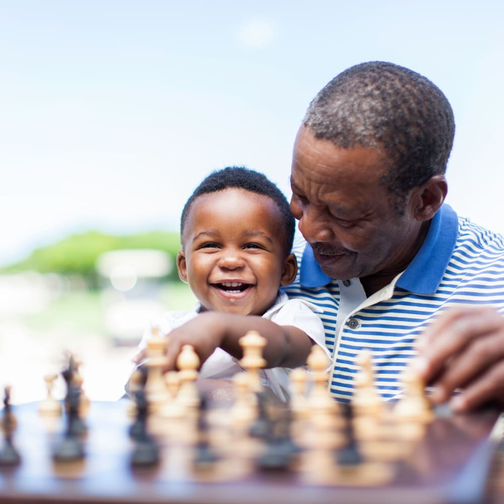 A resident playing chess with his grandson at Alura By Inspired Living in Rockledge, Florida.