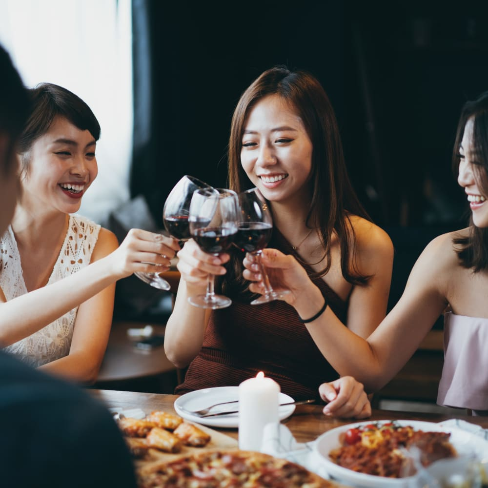 Friends chatting over food and wine at Oaks Minnehaha Longfellow in Minneapolis, Minnesota