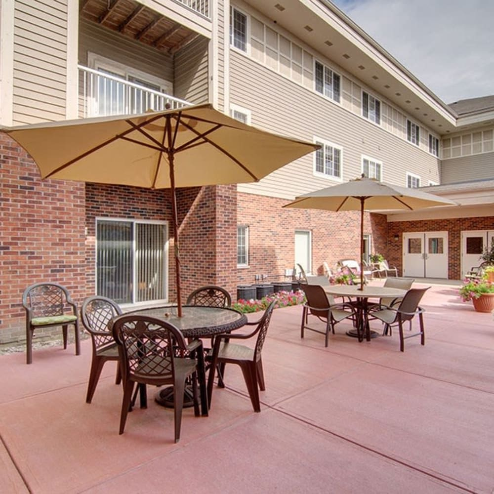 Modern outdoor seating with umbrellas and patio furniture at Randall Residence of McHenry in McHenry, Illinois
