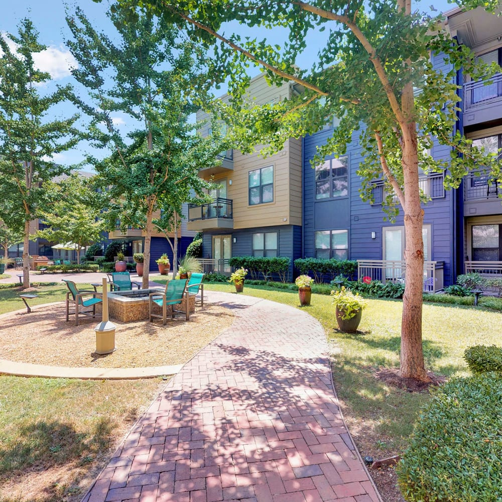 Brick pathway winding through a courtyard surrounded by mature trees at Oaks 5th Street Crossing at City Station in Garland, Texas