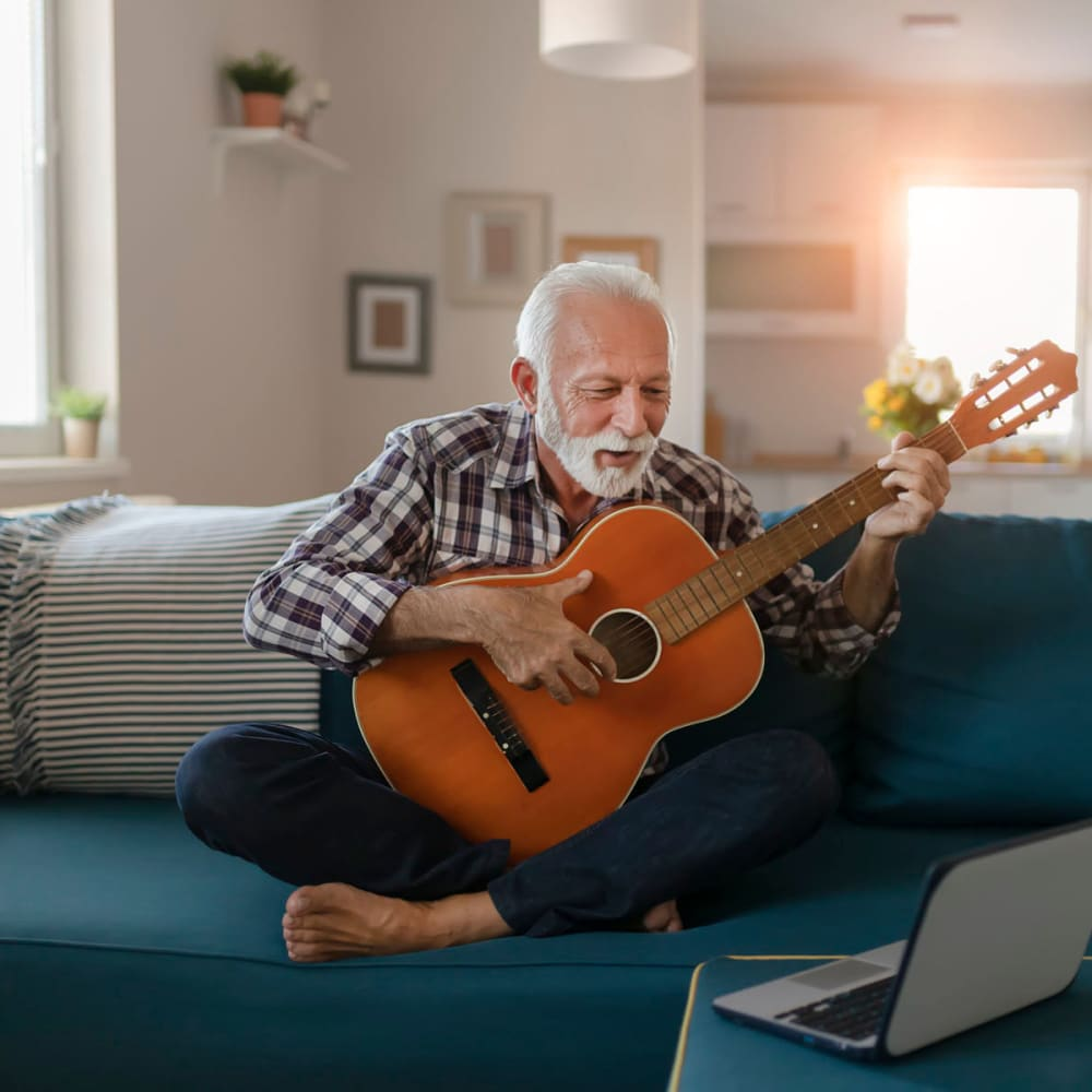 Resident practicing acoustic guitar on the couch in his home at Oaks 5th Street Crossing City Center in Garland, Texas
