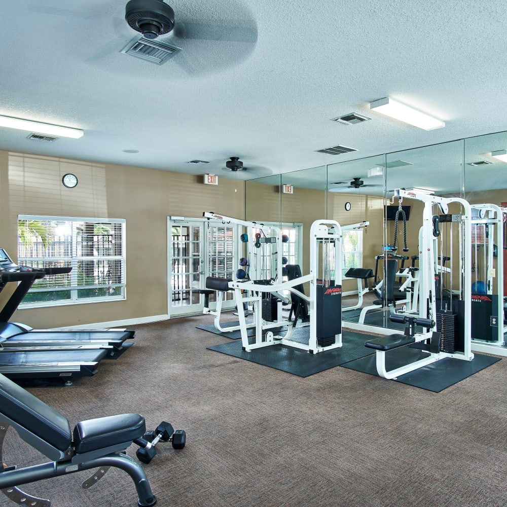 A fitness center with individual workout stations at Calais Park Apartments in St Petersburg, Florida