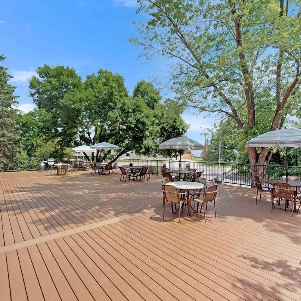 Mature trees providing shade at the decked picnic area at Oaks Braemar in Edina, Minnesota